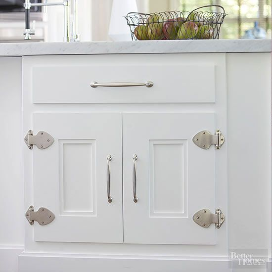 Exposed strap hinges rendered in a high-impact shape and a modern material partner with softly curved chrome pulls to beautifully update white-painted cabinets in a cottage-style kitchen. Note the recessed dual-paneled design that brings a handcrafted look and eye-catching depth to this pair of cabinet doors./