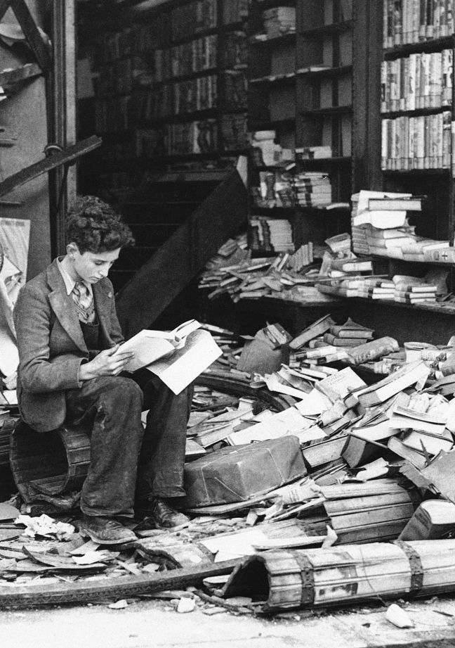 A boy sits amid the ruins of a London bookshop after an air raid. (October, 1940)