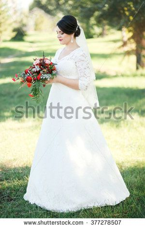 Bride on a background of trees, Fine portrait, full-length. With the wedding bouquet of red flowers.