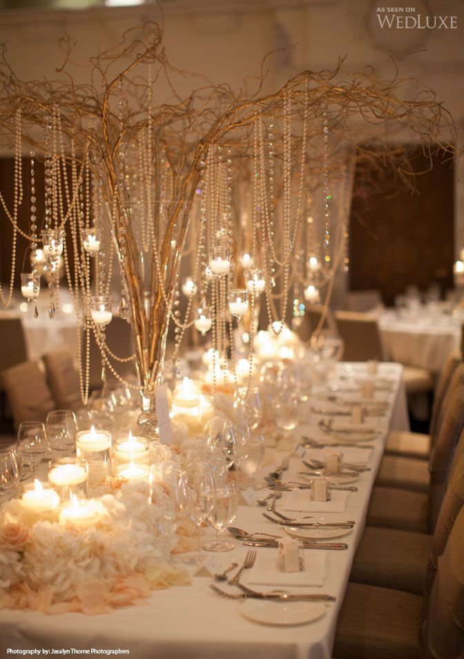 Gold sprayed twigs in tall glass vases with pearl beads and candles.  Lovely design