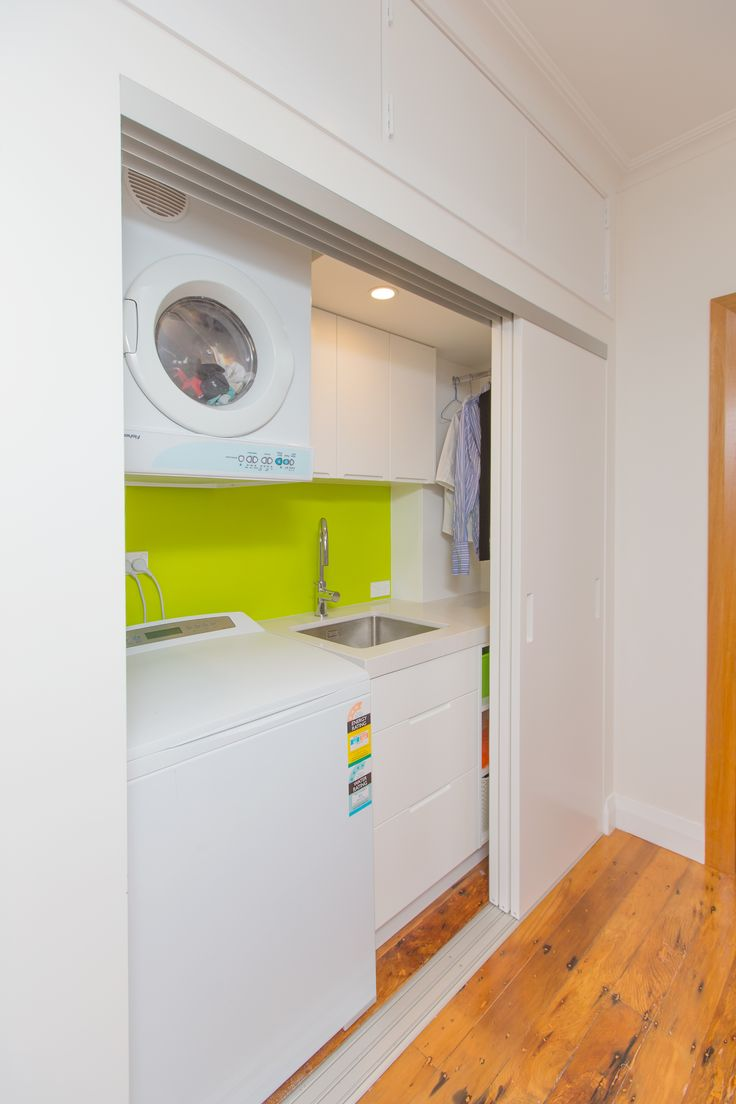 Laundry 451. Sally Steer Design Ltd. Wellington, NZ. laundry in a hallway with triple sliding doors and feature splashback.