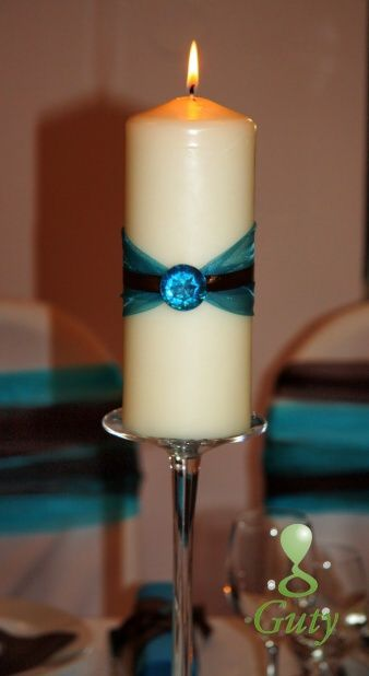 Sviečka dodekorovaná stuhami a diamantom.