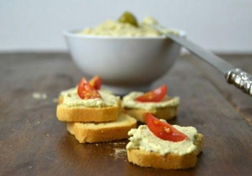 Deshuesar las aceitunas con un cuchillo. En un procesador de alimentos, triturar las aceitunas con las nueces y el aceite de oliva hasta que quede un paté suave. Condimentar. Servir acompañada de galletas o verduritas.