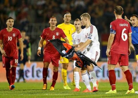 Bekim Balaj of Albania takes a flag depicting so-called Greater Albania, which was flown over the pitch during their Euro 2016 Group I qualifier against Serbia