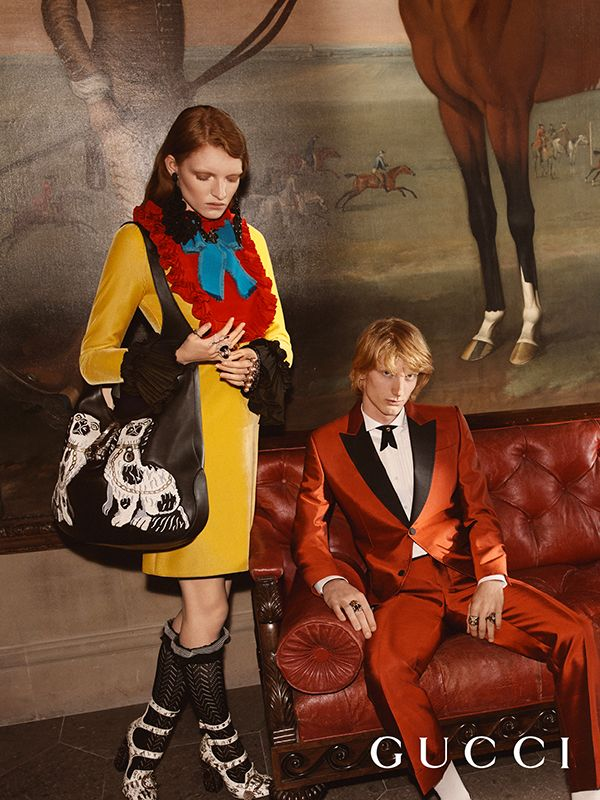 Captured inside Chatsworth House, an image from the Gucci Cruise 17 campaign featuring a red silk tuxedo with contrast lapels, yellow dress with plush cuffs and bow, with the Gucci Dionysus hobo appliquéd with King Charles Spaniels.