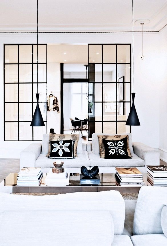 Black and white Scandinavian living room with modern powder coated light fixtures and coffee table books.