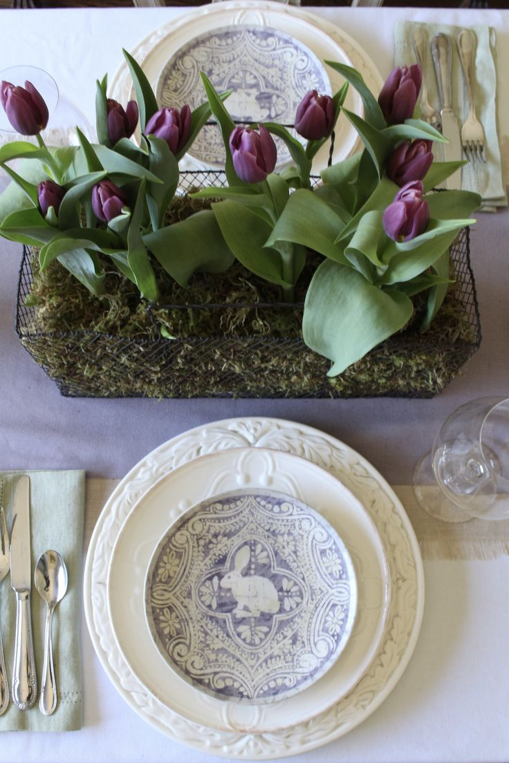 Purple tulips and green moss centerpiece on a lavender runner makes for an easy and elegant Easter table