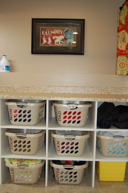 Laundry Folding and Sorting Cubbies. Love the names on the baskets. Great idea.