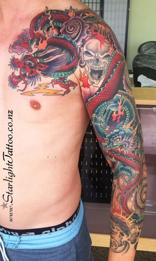 Full Japanese arm sleeve and chest tattoo with dragons and skulls.