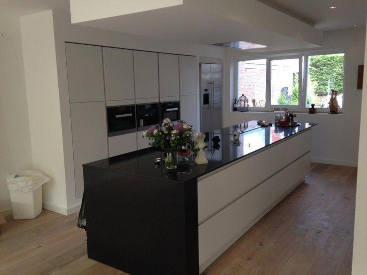 Matlak witte greeploze keuken met composiet werkblad en composieten stol. De keuken is voorzien van Miele apparatuur en een geïntegreerde afzuigunit, welke is bevestigd in een optisch zwevend verlaagd plafond.