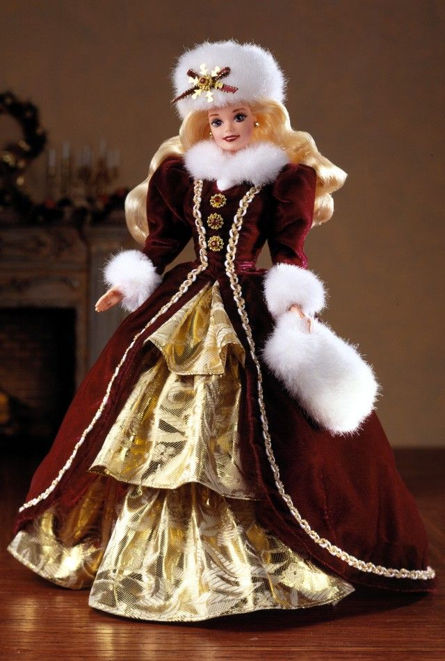 1996 Happy Holidays® Barbie® Doll | Barbie Collector n a charming burgundy velvet coat trimmed in luxurious white faux fur, Barbie® doll welcomes the holiday season. Underneath her lovely velvet coat is a golden-tiered skirt. A gorgeous white faux fur muff and hat match the fur accents at her collar and sleeves.