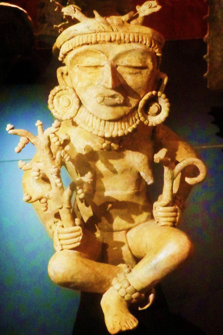 Deze zittende figuur draagt grote oorpluggen, opvallende lipsieraden, een ketting en arm- en enkelbanden. Op zijn hoofdtooi zijn twee slangen afgebeeld. In zijn handen houdt hij planten vast.