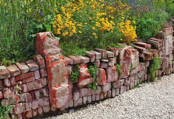 С подпорной стенкой сухой кладки, сделанной из старых кирпичей и массивных фрагментов кирпичной кладки, цветник выглядит стильно и эксклюзивно.