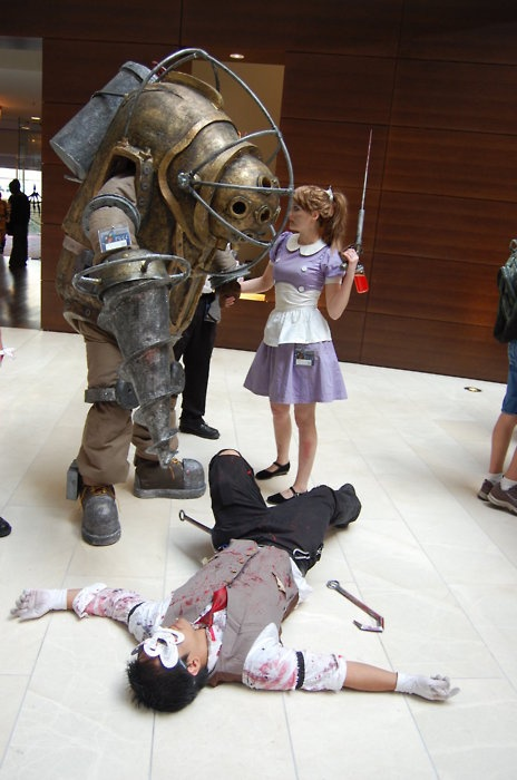 A Big Daddy and Little Sister stand over the corpse of a splicer.