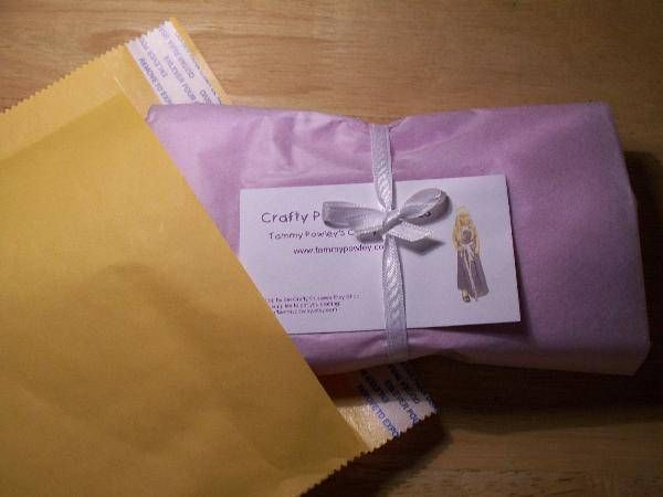 jewelry item goes in small zip lock bag, including swag; zip lock bag goes in organza; organza bag is placed on top of folded receipt; wrap in tissue; tie with ribbon; slip in card; pop into addressed mailer
