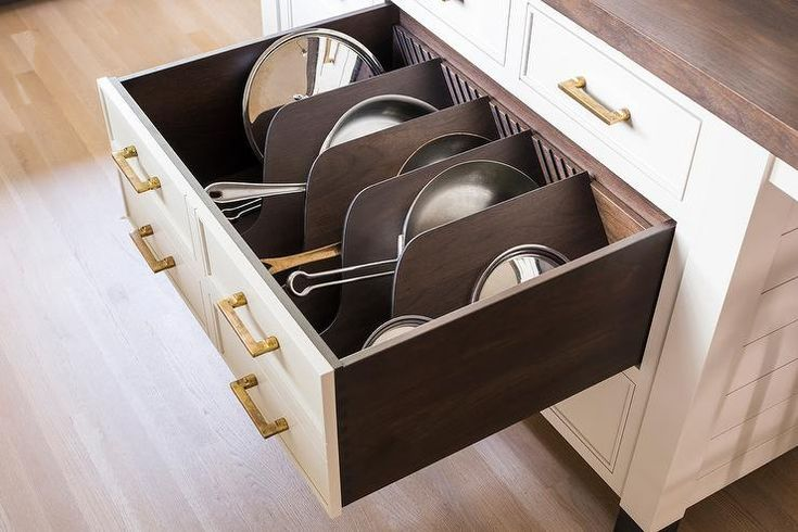 A white shiplap kitchen island accented with a stained wood butcher block top boasts white drawers accented with antique brass hardware and fitted with custom pat and pan lid dividers.