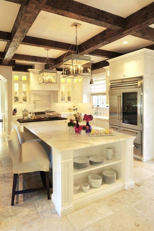 We love this gorgeous white kitchen with a beamed ceiling and marble countertops. Upholstered counter height bar stools are the perfect complement.