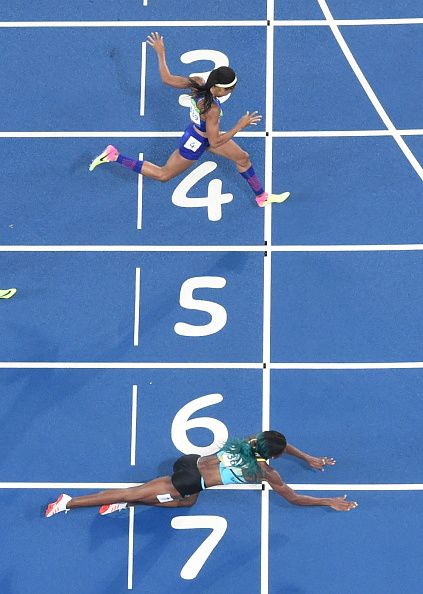 #TOPSHOT Bahamas' Shaunae Miller dives to cross the finish line ahead of USA's Chase Kalisz during the Women's 400m Final during the...