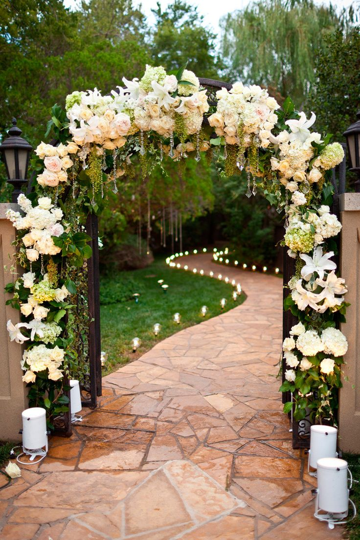 Floral arch entry to ceremony with candlelit path into backyard reception.