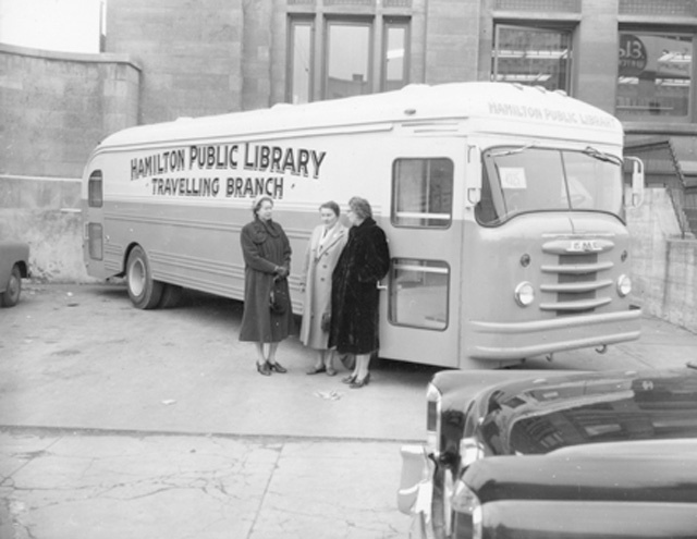 "The first travelling branch was a bus-like vehicle staffed by a librarian and equipped with a selection of books to give those not able to visit the main library, or one of the branches, a chance to become a member of the library. Its purpose was also an effort to meet the unattained standard of ""service within one mile of the home."" Here staff from the Hamilton Public Library, including Chief Librarian Freda Waldon (in black coat) prepare for the official launch on December 4, 1956."