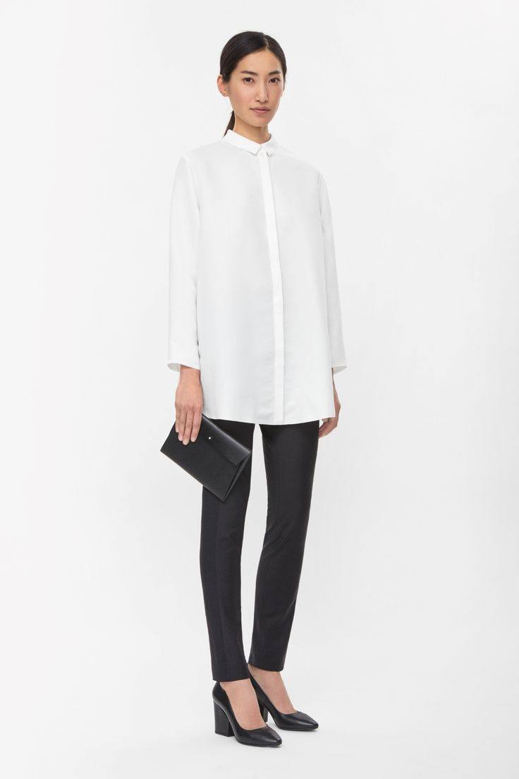 Made from soft, fluid fabric, this long shirt is an oversized style with clean glued edges. A loose fit, it has a hidden front button fastening, long sleeves and a curved hemline that is lightly shorter at the back.