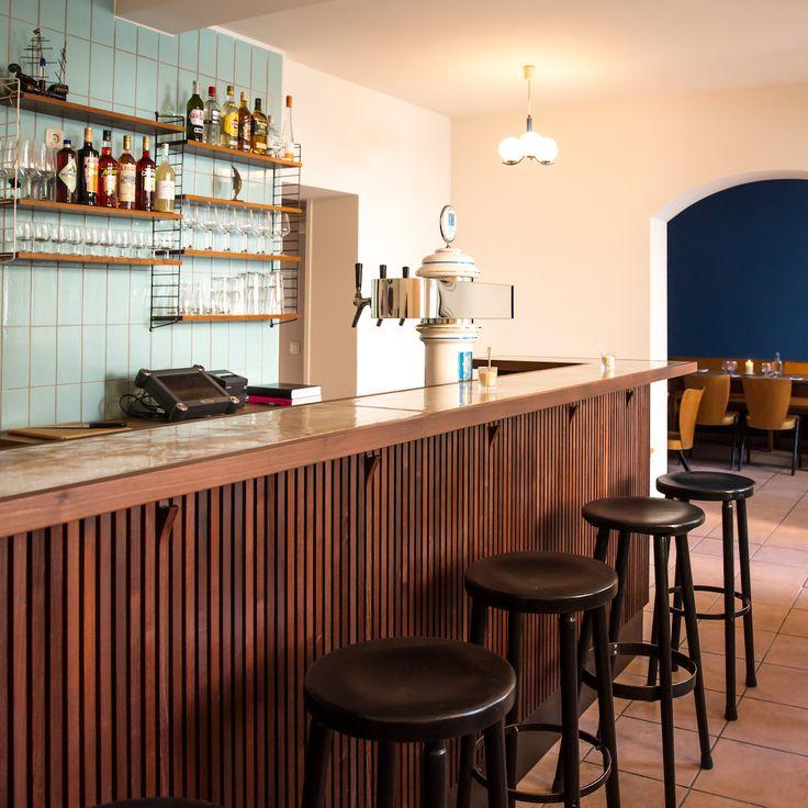 Die Bar im Restaurant Polka in München Haidhausen, mit türkiesen Fliesen und Tresen aus Holz