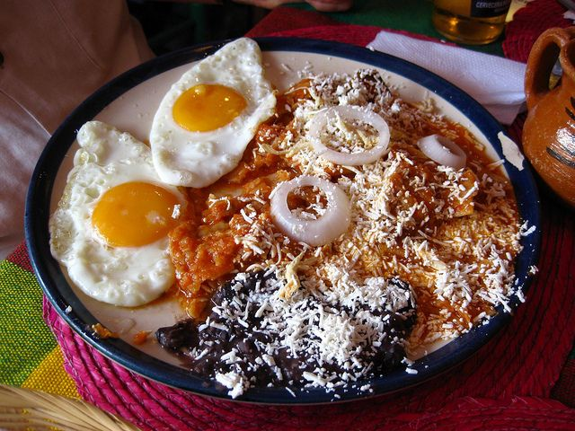 Chilaquiles rojos con huevos estrellados y frijolitos refritos negros   (Red Chilaquiles with fried eggs and black refried beans)