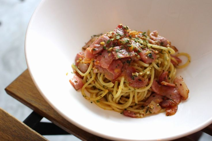 """""""Spaghetti Aglio e Olio"""" is a traditional Italian pasta dish, made by lightly sauteeing pressed garlic in olive oil (sometimes with the addition of dried red chili flakes) and tossing with spaghetti. Shown here topped with thin slices of pan-seared ham and juicy back bacon."""