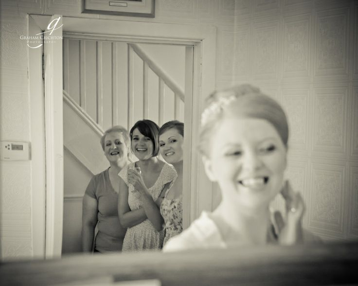 Bride checking her make up in the mirror with her bridesmaids looking on through a doorway. www.grahamcrichton.com