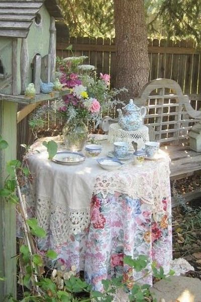 A table dressed with fabric and flowers; tea served in nice china in a quiet spot in the garden