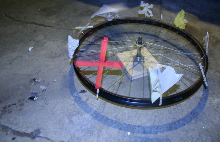 Author: Kory A. Beighle      Date: 09 April 2011      salvaged bike wheel; wood, cloth, metal, paper and hardware     how can you destabalize the linearity of a narrative sequence?      the human experience is a continuous unfolding; a process of becoming-ever-different.  the form of our experience is the form of existance;  the form of any      narrative is inherently related to the process of the stories unfolding.  the non-linear sequence acknowledges our role in the act of experiencing.