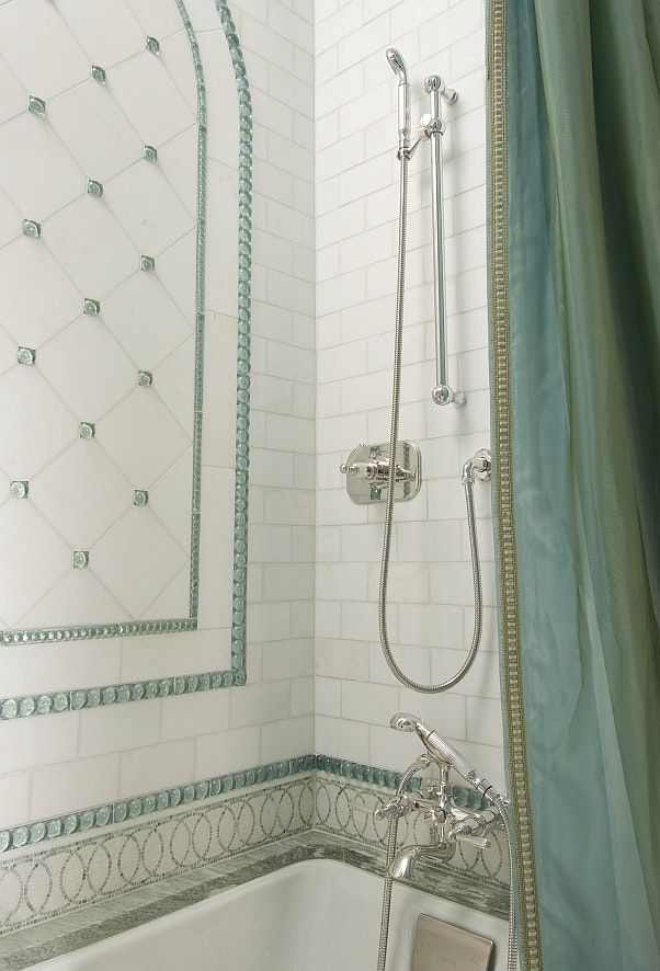 The tub/shower is lined with White Thassos and Ming green mosaic tiles combined with iridescent glass insets.