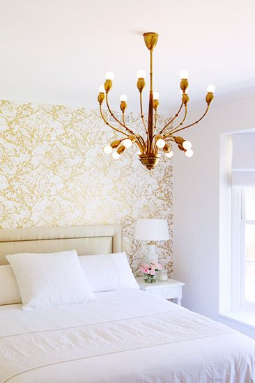 White + gold bedroom with wallpaper accent wall and amazing gold chandelier