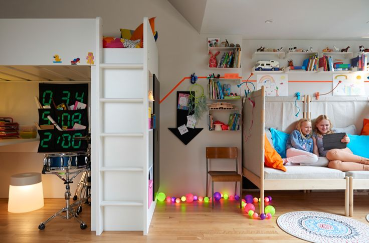 """Blick auf ein gemeinsames Kinderzimmer mit STUVA Hochbettgestell mit Arbeitsplatz und Aufbewahrung in Weiß. Zwei Mädchen sitzen auf IKEA PS 2014 Ecksesseln mit Stoffbezug """"Risane"""" natur und entspannen sich mit einem Tablet-PC. An den Wänden befinden sich Regale, auf dem Boden liegen Lichterketten."""
