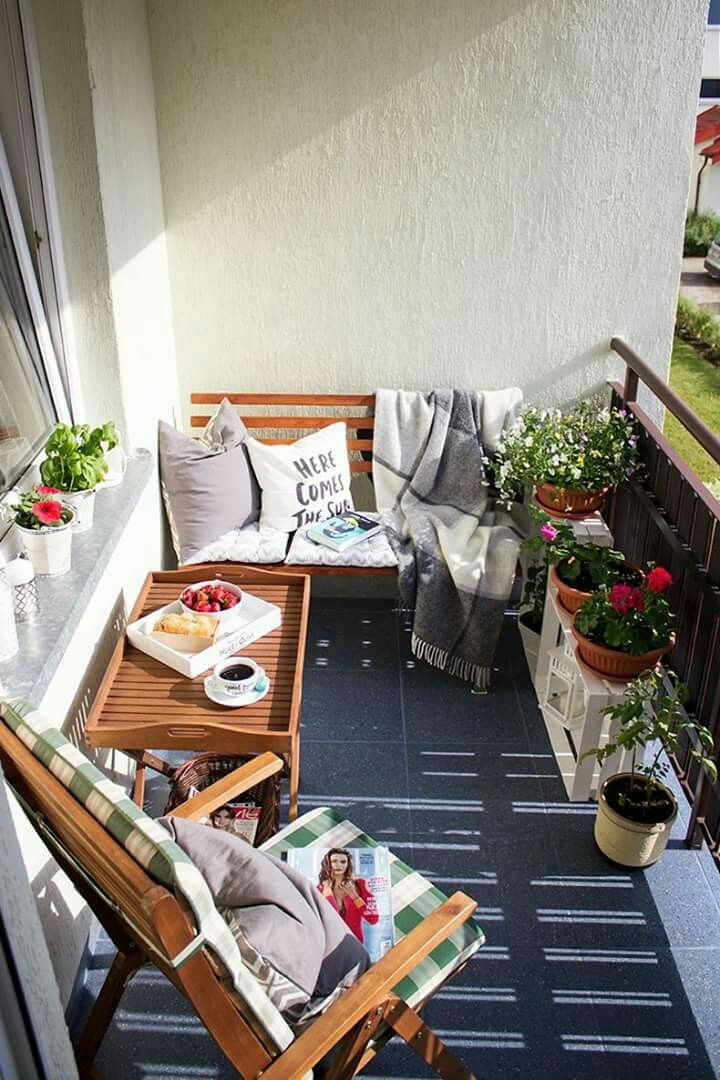 balcony with wooden bench, serving tray, and wooden chair and plants
