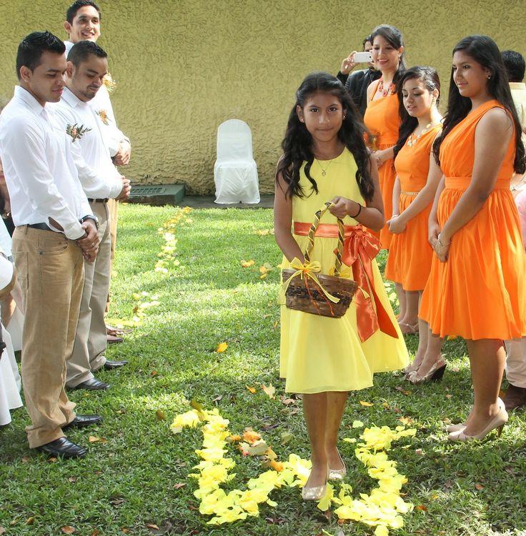 Las damas en naranja, los caballeros pantalón beige y camisa blanca y las niñas de amarillo con naranja. Absolutamente divinos