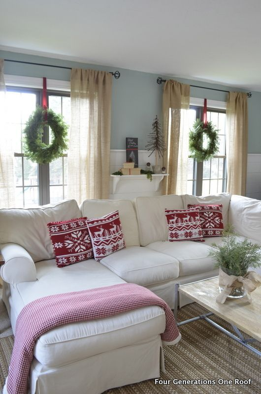 A pretty red and white christmas living room with green wreaths on the windows. Love the idea of using red ribbon to hang the wreaths.