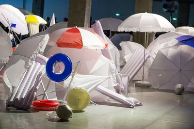 Défilé Jacquemus printemps-été 2015. Au premier étage de la Cité de la Mode et du Design, le chant des grillons et le bruit des vagues réchauffent l'atmosphère. Au centre de l'immense salle en béton, un joyeux fourbi de parasols, matelas gonflables, bouées et flotteurs semble avoir été balayé par le Mistral.