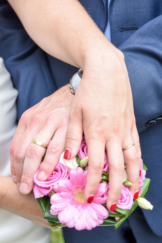 Bride and groom Wedding rings hands on the bouquet by Anais Photography.