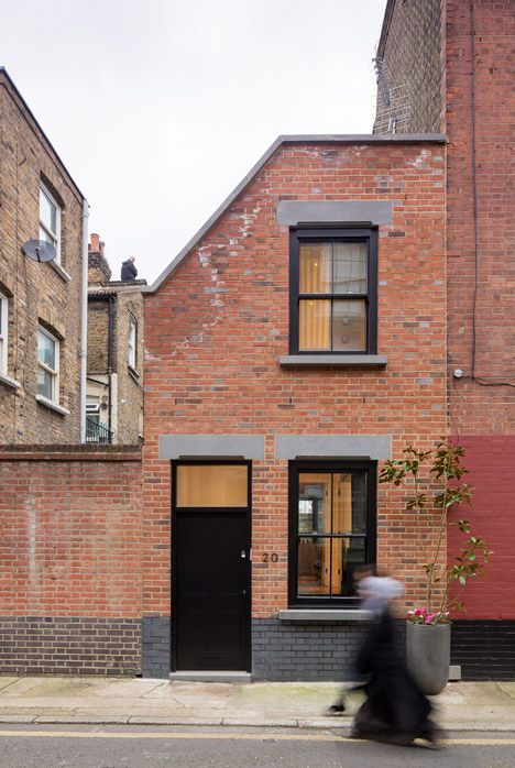 Old upholsterer's workshop in London transformed into a narrow brick home.