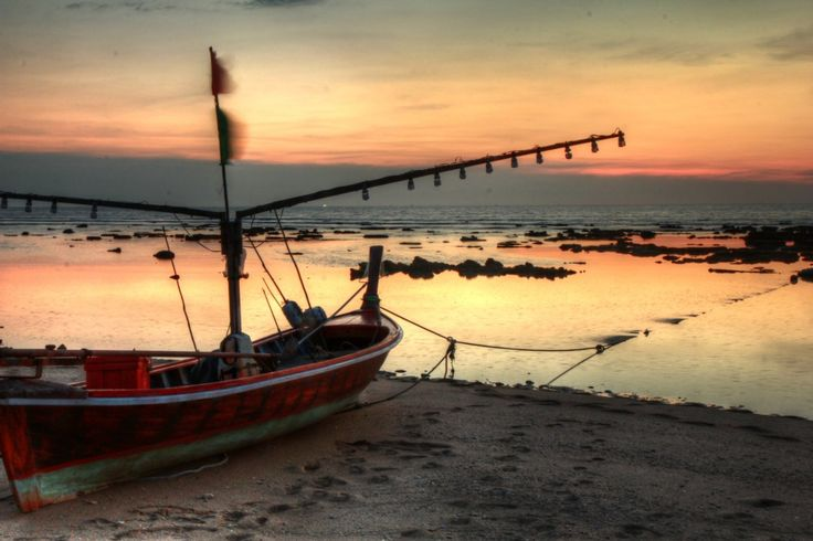 Sunset over beach in thailand, with a fisherman's boat in the foreground.