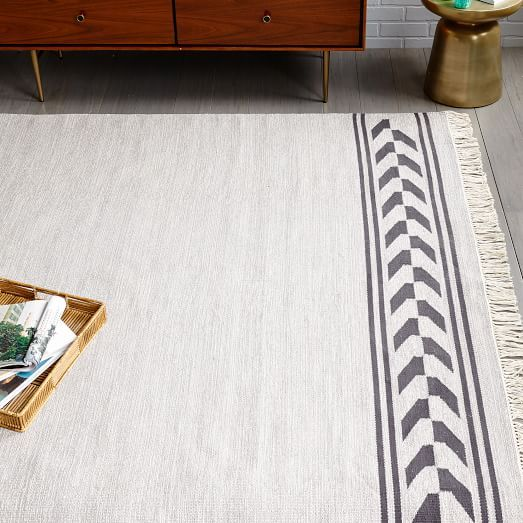 A neutral rug grounds a room that's filled with color—we chose the Steven Alan Arrow Border Cotton Kilim Rug.