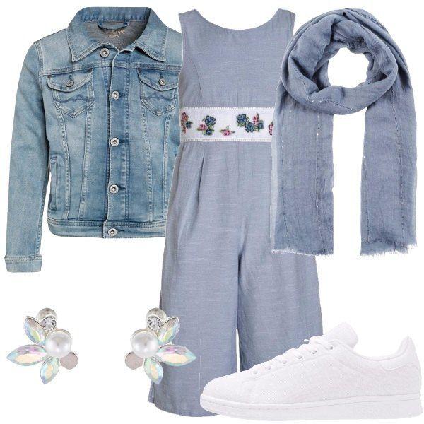 Una ragazzina davvero alla moda che indossa: jumpsuit in cotone, con fascia in vita a motivo floreale, giubbino in denim, sciarpa con piccole paillettes applicate, sneakers bianche e orecchini a lobo a forma di fiore.