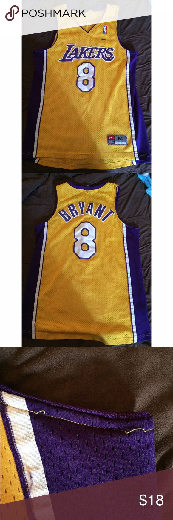 Lakers Kobe Bryant Jersey Lakers Kobe Bryant jersey #8. Used but still in good condition. The only two issues I could find on the shirt were the threading around the sleeve and a small stain on the bottom back of the shirt. Posted pictures of these problems. Price reflects these issues. Nike Tops