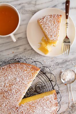 Passion Fruit-Yogurt Cake~ 4 ounces (1 stick) unsalted butter, melted, plus more for greasing the pan, 10 ounces cake flour, 1 teaspoon baking powder, ½ teaspoon baking soda, 5 large eggs, at room temperature, 10 ounces sugar, 6 ounces plain yogurt, at room temperature, 5 ounces passion fruit puree, Powdered sugar, for dusting.