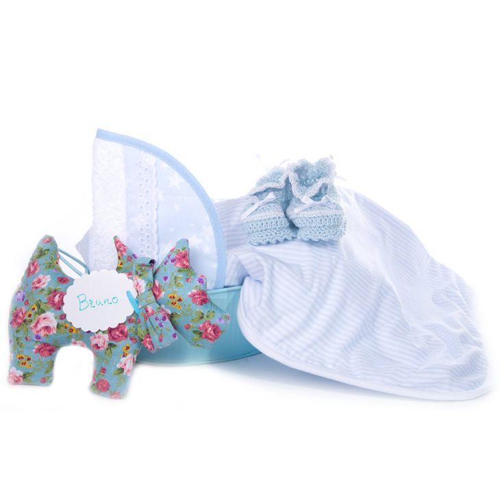 Cuévano de latón azul, arrullo de algodón, babero, patucos, perrito con el nombre del bebé, felicitación personalizada