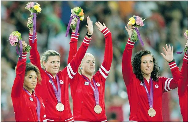 Canadian women's soccer team members Desiree Scott, Christine Sinclair, Sophie Schmidt and Melissa Tancredi wave after being presented with their Bronze medals at the Olympic Games in London on Aug. 9.