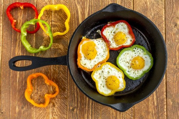 40299811 - large cast iron skillet with fried eggs in green, yellow, red and orange bell peppers sitting on wooden table with pepper slices