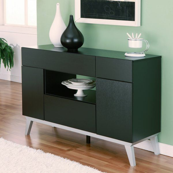 The Sideboard is a modern cabinet, perfect for organizing and storing essentials for your next dinner party. Its features include three drawers for storing silverware and dining linen, cabinets for storing flatware, and an open compartment/shelf for display or storage. Featuring a rich black finish, this contemporary piece is a lovely addition to any home.