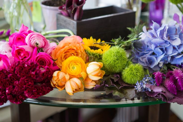 Organize a rainbow arrangement easily by choosing your flowers first, laying them out in the order you want them to appear, and then building a bouquet from there.